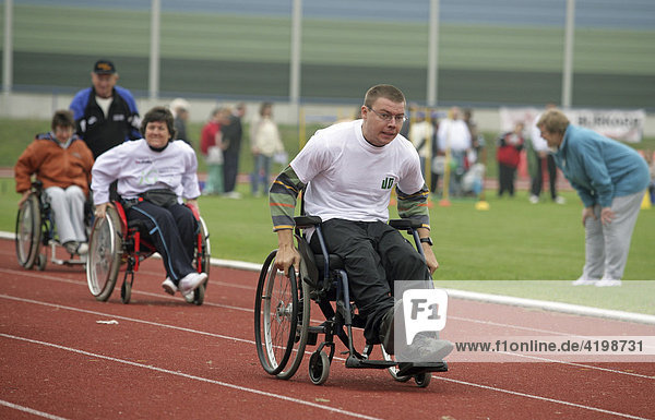 Ein behinderter Mann macht mit seinem Ruhlstuhl bei einem Wettrennen mit
