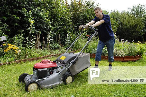 Jugendlicher mäht den Rasen
