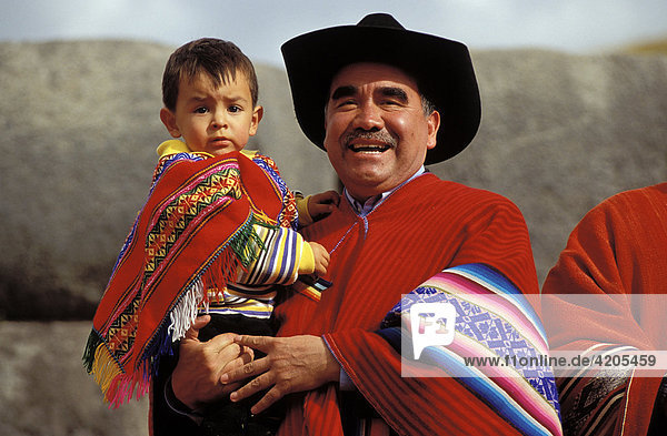 Mann mit Kind auf dem Arm. Vater und Sohn in landestypischer Kleidung   Südamerika  Peru   Anden