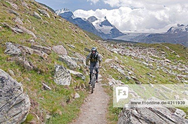 Elijah Weber mountain biking the Kristallweg Trail below Rothorn Paradise in the Swiss Alps high above the town of Zermatt Switzerland