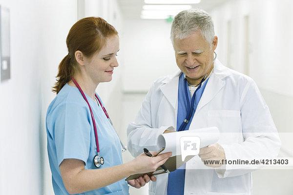 Arzt und Krankenschwester besprechen Krankengeschichte