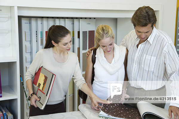 Frau unterstützt Paar bei der Auswahl von Tapetenmustern im Geschäft