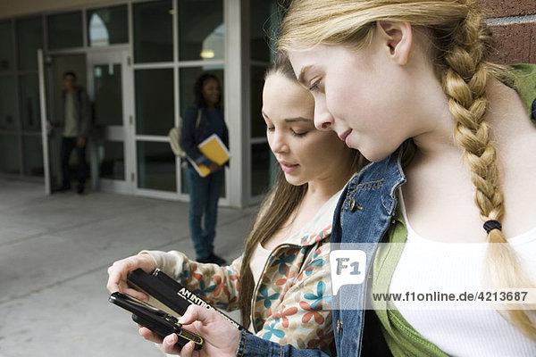 Junge Frau zeigt Freund Handy