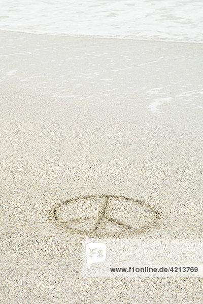 Friedensschild im Sand am Strand gezeichnet Friedensschild im Sand am Strand gezeichnet
