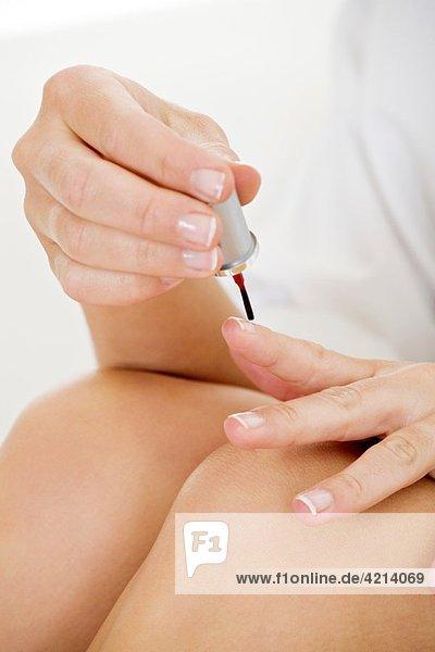 Beautiful Caucasian woman applying finger nail polish