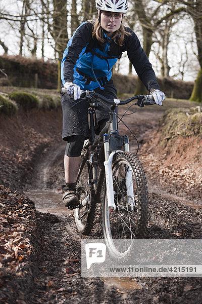 Frau beim Mountainbike fahren auf schlammiger Strecke