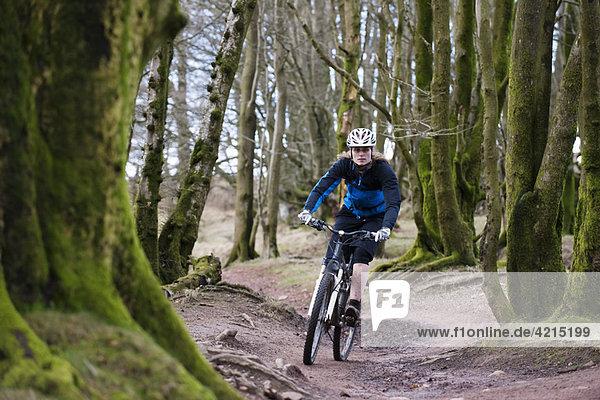 Frau beim Mountainbiken im Wald