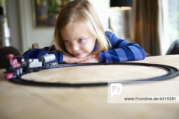 Mädchen spielt mit einer Spielzeugeisenbahn