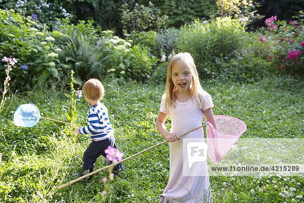 Bruder und Schwester mit Schmetterlingsnetzen