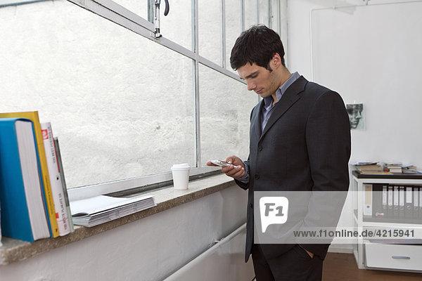 Ein Mann  der einen Text auf seinem Handy schreibt.