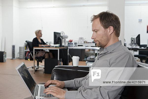 Mann entspannt auf Sofa mit Laptop
