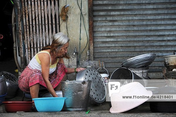 Thai woman washes dinnerware on the roadside
