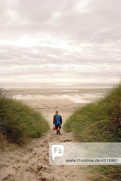 9 year boy walking through sand dunes away from beach carrying bucket