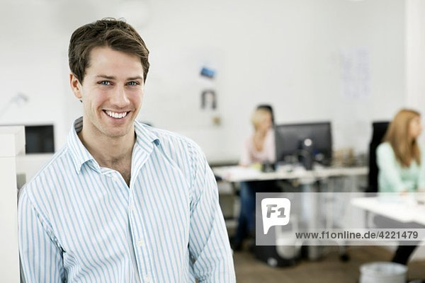 Glücklicher Geschäftsmann steht im Büro