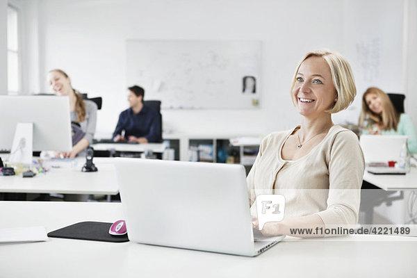 Glückliche Geschäftsfrau am Schreibtisch
