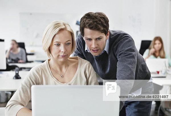 Mann hilft Kollege mit Computer
