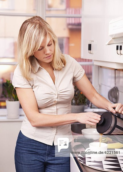 Frau gießt Kaffee in die Tasse
