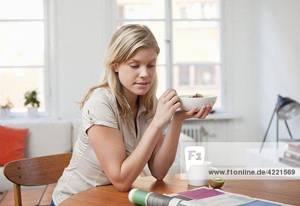 Frau beim Frühstücken und Zeitungslesen
