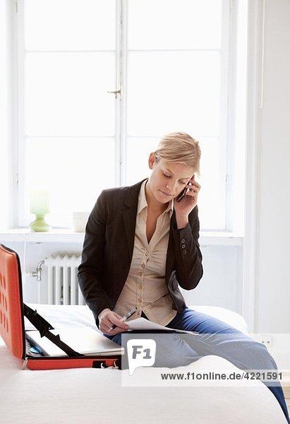 Frau im Bett sitzend mit Laptop und Handy
