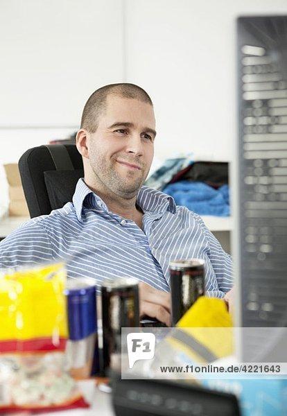 Mann lächelt hinter dem Computer
