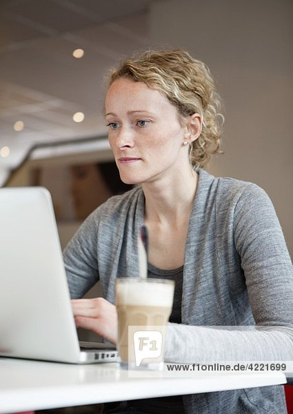 Woman with laptop at coffeehouse