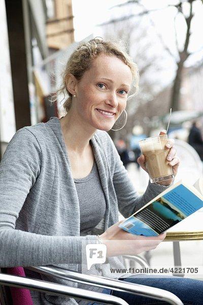Frau liest Buch im Kaffeehaus