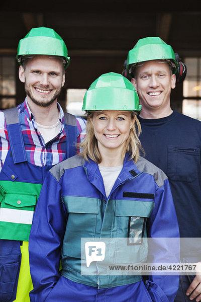 Drei Arbeiter in Helmen Drei Arbeiter in Helmen