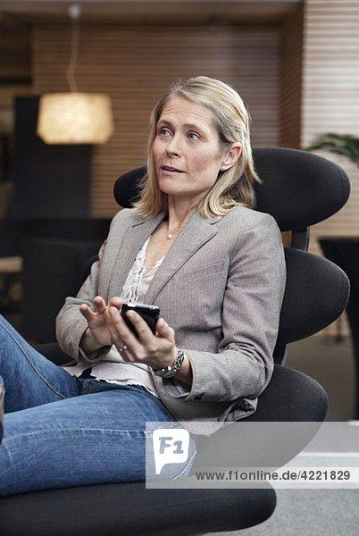 Frau im Stuhl sitzend mit Handy