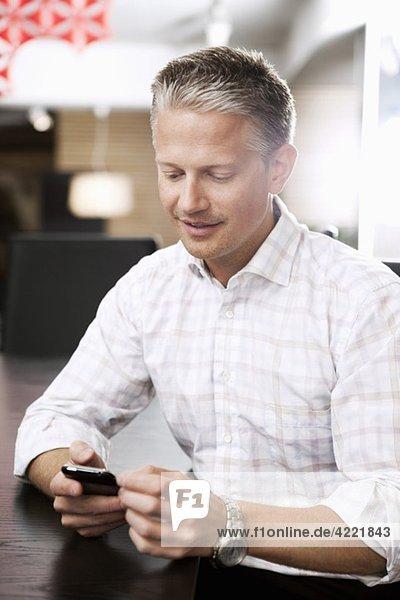 Man writing on phone at work
