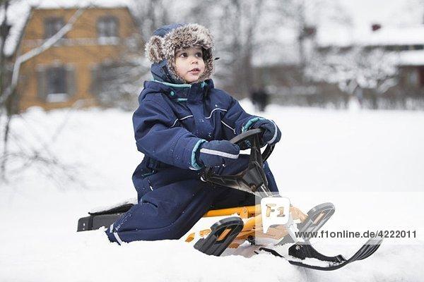 Junge auf Snowracer