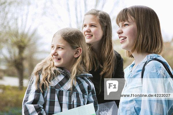 Drei Mädchen  die zur Seite schauen