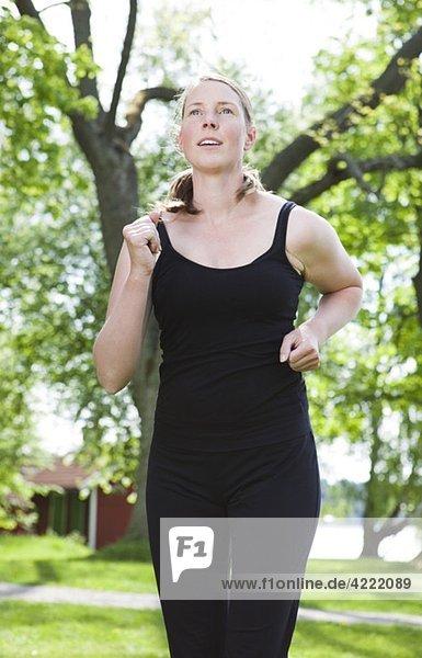 Frau in schwarz läuft im Park