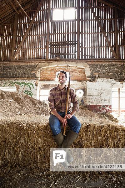 Bauer auf Heuballen sitzend