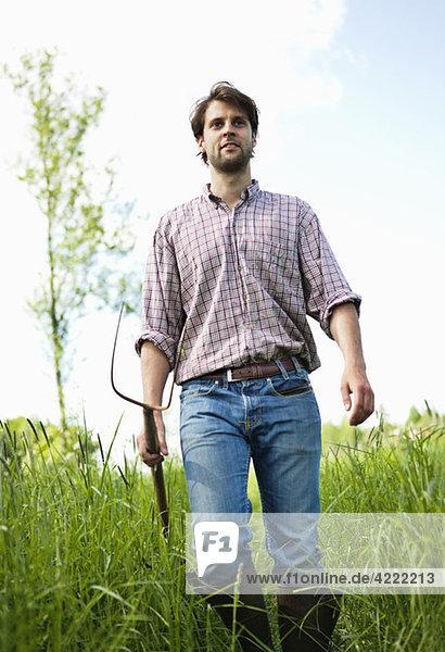Mann mit Heugabel im hohen Gras