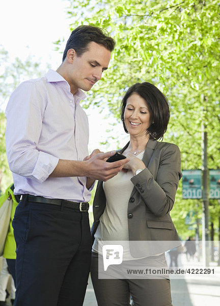 Businessman and businesswoman looking at telephone