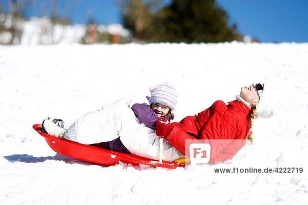 Mother and daughter smiling on an sledge in the snow