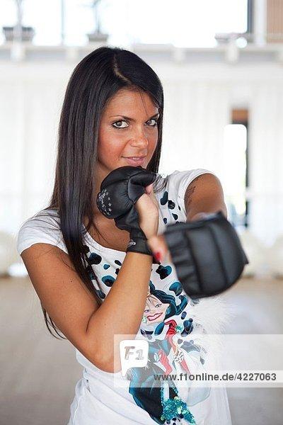 Brunette wearing black gloves for kick boxing training