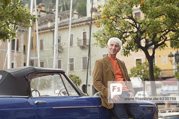 Senior lehnt an Oldtimer am Hafen  Italien  Linfano