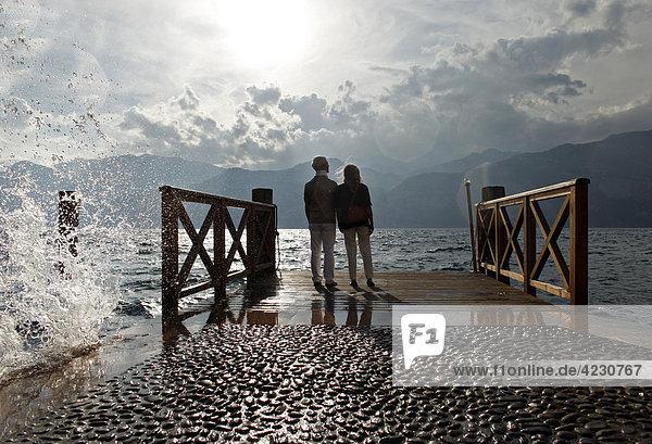 Seniorenpaar bei Sonnenuntergang schaut aufs Wasser  Italien  Malcesine