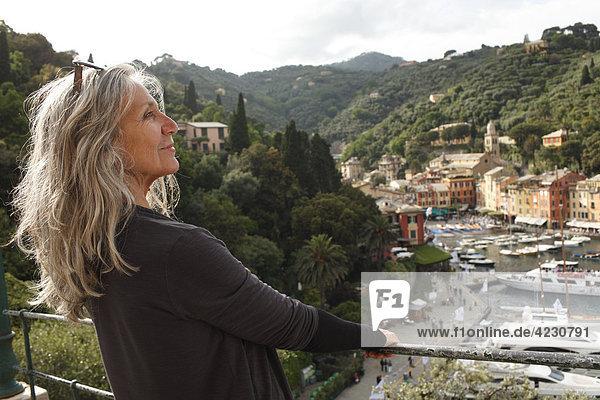 Seniorin schaut auf Hafen und Häuser  Italien  Portofino