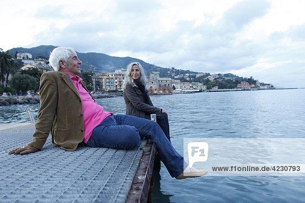 Seniorenpaar sitzt auf einem Steg am Wasser  Italien  Rapallo