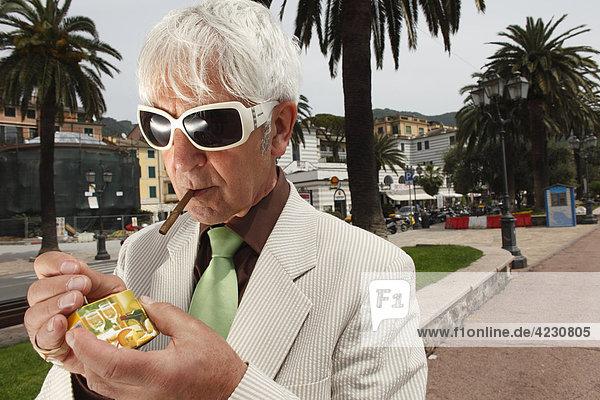 Senior man lighting a cigarillo  Italy  Rapallo