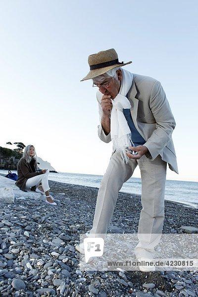Senior schaut auf Steine am Strand  Italien  Sori