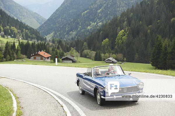 Seniorenpaar fährt mit Cabrio auf Landstraße  Italien  Telve