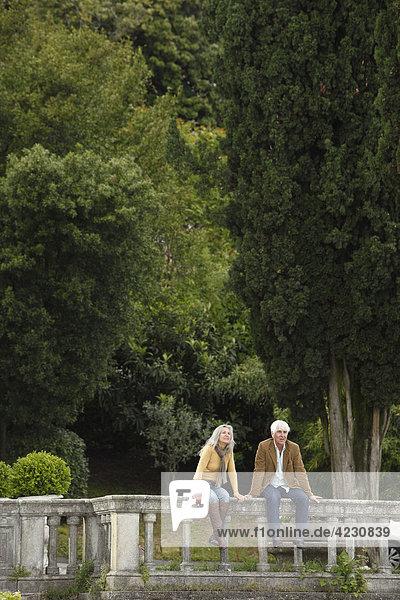 Seniorenpaar sitzt auf einem Geländer vor Bäumen  Italien  Gardone Riviera