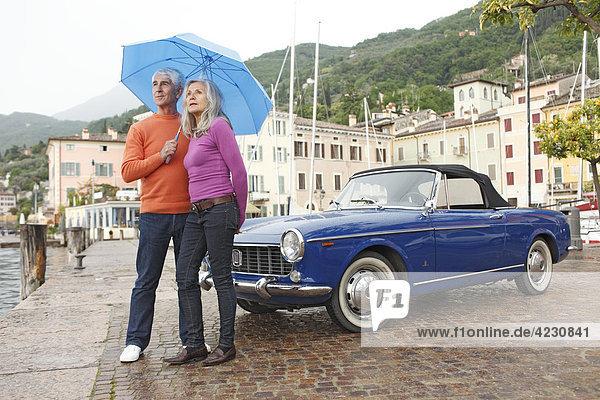 Seniorenpaar mit Oldtimer und Regenschirm am Hafen  Italien  Gargnano  Gardasee