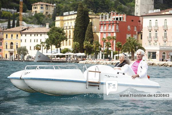 Seniorenpaar mit Tretboot auf dem Wasser  Italien  Riva del Garda  Gardasee