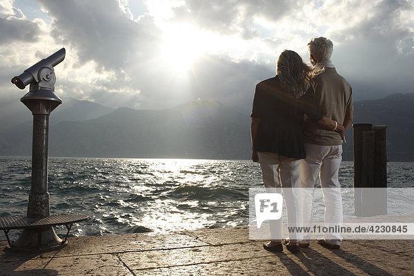 Seniorenpaar bei Sonnenuntergang schaut aufs Wasser  Italien  Malcesine  Gardasee