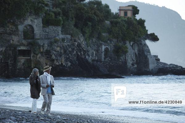 Seniorenpaar geht am Strand spazieren  Italien  Sori