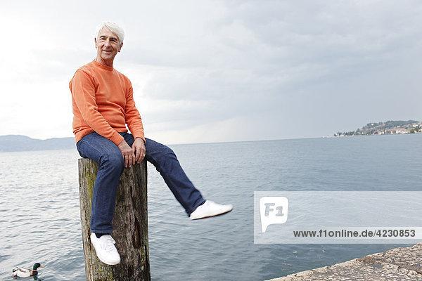 Senior sitzt auf einer Buhne am Wasser  Italien  Gargnano